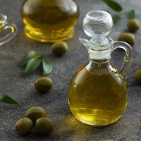 ظرف روغن زیتون در کنار برگ و میوه زیتون - خواص روغن زیتون