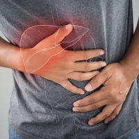 مردی با تیشرت توسی که از شدت درد دستش بر روی شکم و منطقه صفرایش است